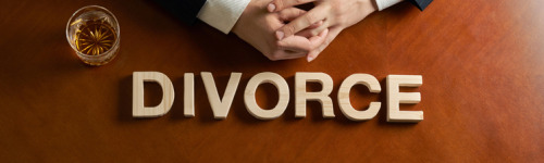 Man Contemplating Divorce  looking down at table with the word divorce spelled out