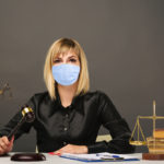 A young fair woman judge in protective mask works in her office.